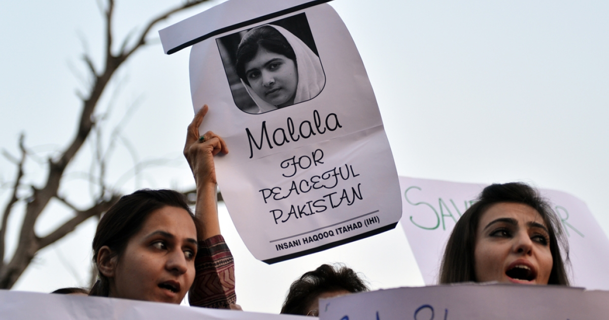 Pakistani civil society activists carry placards with a photograph of the gunshot victim Malala Yousafzai as they shout anti-Taliban slogans during a protest rally against the assassination attempt on Malala Yousafzai, in Islamabad on October 10, 2012. Pakistani doctors removed a bullet from a 14-year-old child campaigner shot by the Taliban in a horrific attack condemned by national leaders and rights activists.</p>