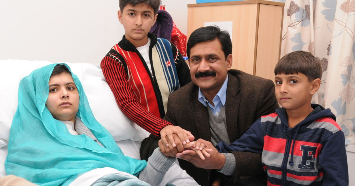 In this handout photo provided by the Queen Elizabeth Hospital Birmingham, Malala Yousafzai sits with her father Ziauddin and her two younger brothers, Atal Khan, right, and Khushal Khan on October 26, 2012 in Birmingham, United Kingdom.</p>