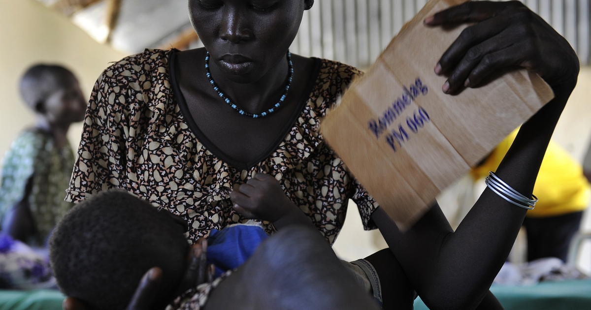 A young Sudanese woman uses a piece of carton to fan her feverish son aling from malaria in South Sudan, on November 10, 2011.  One in seven children die in South Sudan before their fifth birthday, according to UN figures. In this remote village, alongside one of the world's largest freshwater marshes, the mosquito-borne disease is often deadly.</p>
