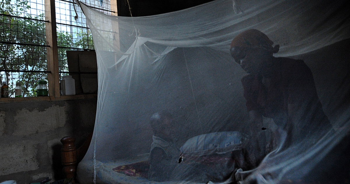 A mother and her child sit on a bed covered with a mosquito net in Tanzanian  where a pioneering vaccine against malaria is in being tested at the government-run Ifakara Health Institute.</p>