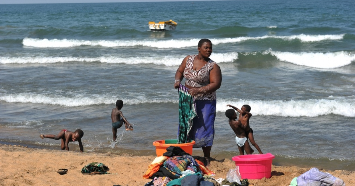 A woman washes clothes as children play along the Saga beach, at Lake Malawi, on July 17, 2011.</p>