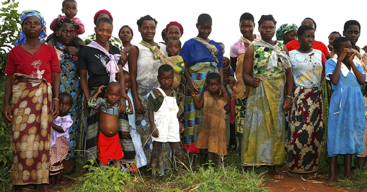 Local women and children, dressed conservatively in long skirts and dresses, gather as Madonna visits their village on the outskirts of Lilongwe, Malawi.</p>