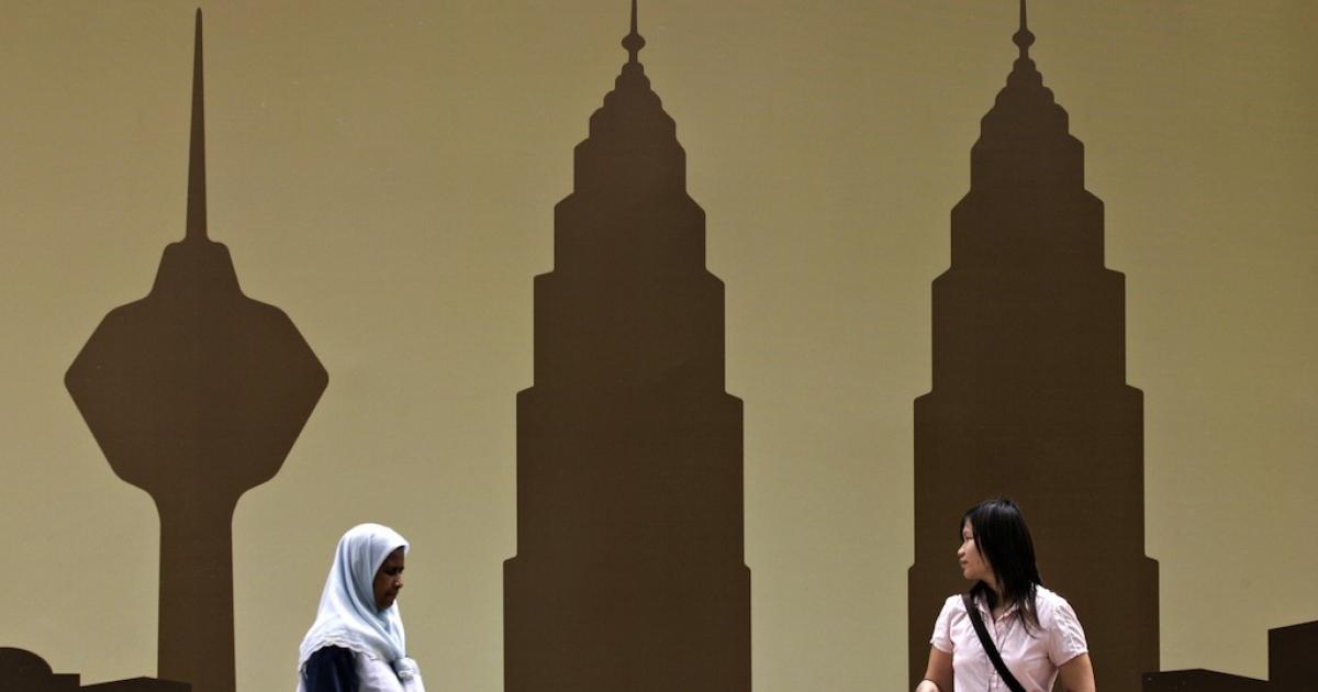 Pedestrians walk past a billboard displaying the Kuala Lumpur skyline with the landmark Petronas Twin Towers (R) and the KL Tower (L) in downtown Kuala Lumpur, January 3, 2008.</p>