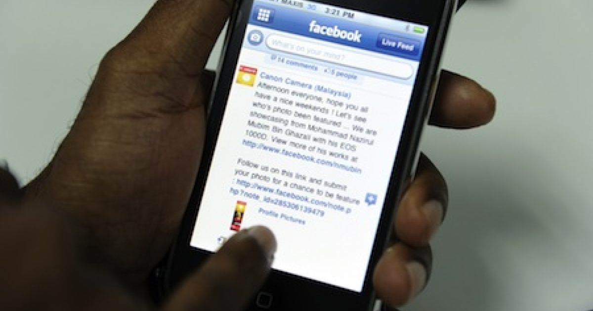 A man browses Facebook on his mobile phone in Kuala Lumpur, Malaysia.</p>