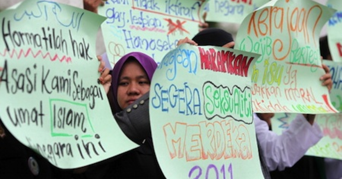 Protesters raise placards during a protest outside a corridor Mosque in Shah Alam near Kuala Lumpur on November 4, 2011. Demonstrators urged the goverment to give recognition to the lesbian, gay, bisexual and transgender (LGBT) community.</p>