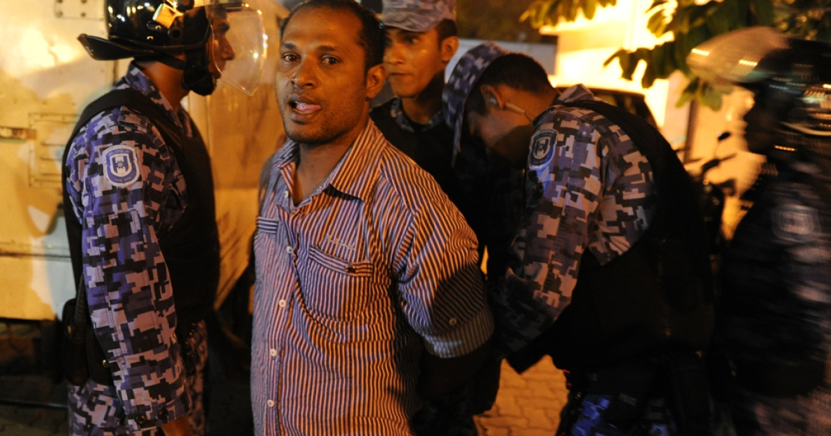 Police officers arrest a supporter of Maldives' former President Mohamed Nasheed during a protest in Male on Feb. 12, 2012.</p>