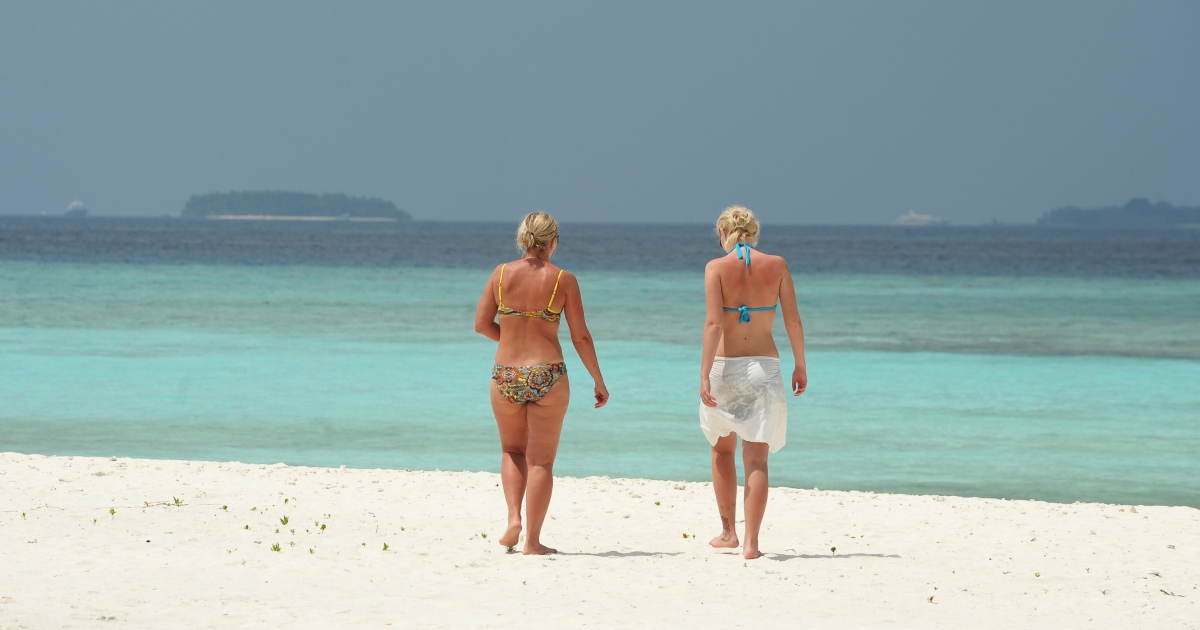 Unidentified foreign tourists walk along a beach of the Paradise Island Resort and Spa in the North Male' Atoll on February 14, 2012 as the equatorial nation is gripped by a major political crisis.</p>