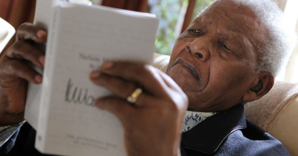 Nelson Mandela looks at a copy of his latest book