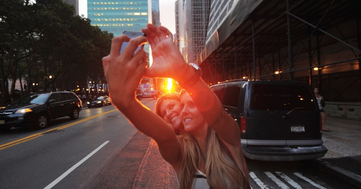 Two women photograph themselves during the Manhattanhenge sunset in New York City on July 13, 2011.</p>