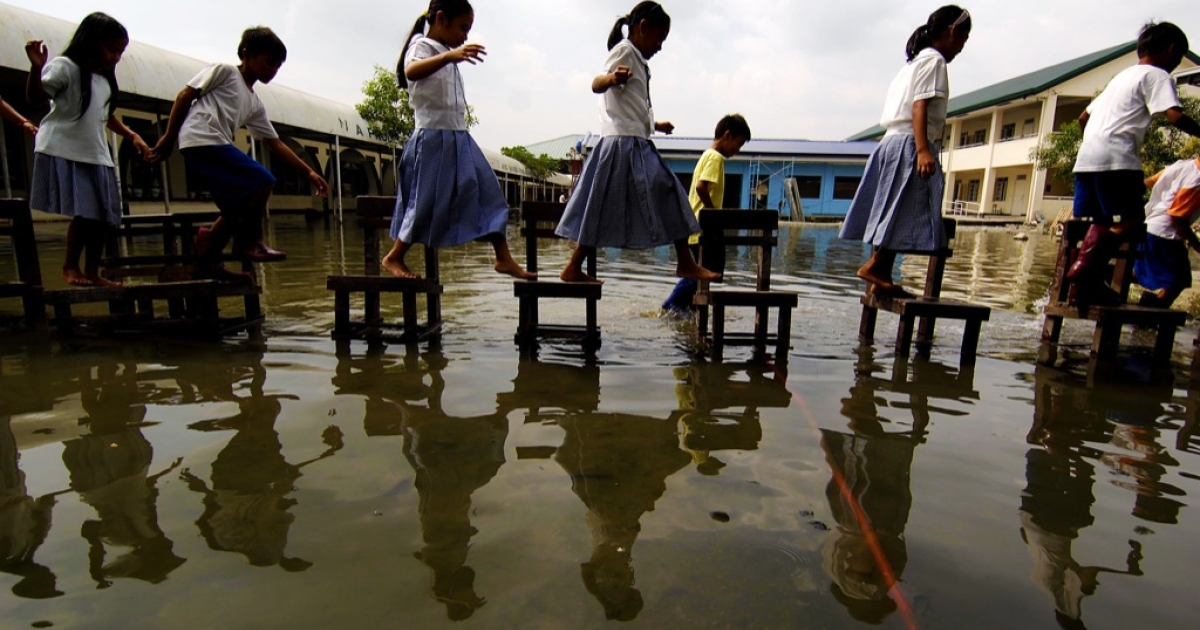 Filipino elementary school students use chairs to cross a flooded yard inside their school grounds on October 20, 2009 in Taytay, Philippines (Rizal province east of Manila).</p>