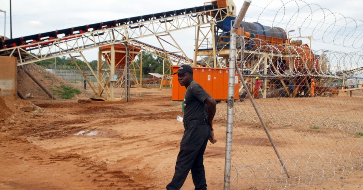 A private security employee guards on December 14, 2011 a diamond processing plant in the diamond-rich eastern Marange region, where families were expulsed from their house to make way for excavation machines of major mining companies allied to the regime of President Robert Mugabe.</p>