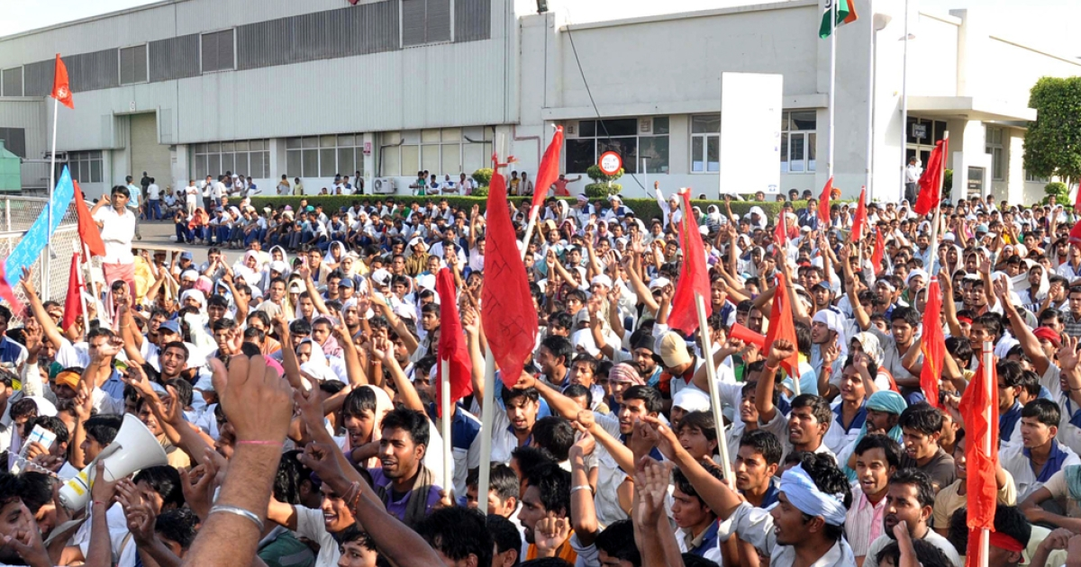 Indian workers shout slogans as they wave flags outside a Maruti-Suzuki vehicle plant at Manesar, on the outskirts of New Delhi on October 14, 2011. 40 people were injured and one killed in clashes between the protesting workers and managers and executives on July 18, 2012 at the same plant.</p>