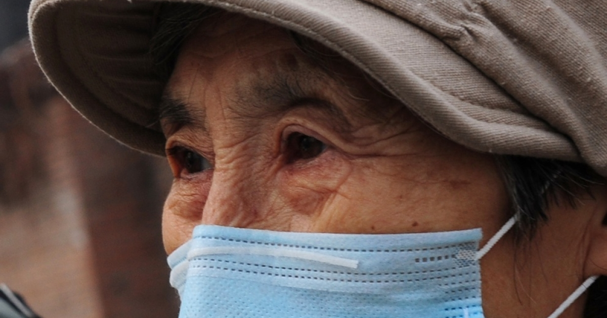 An elderly woman wears a mask as protection against air pollution in Beijing on Nov. 22, 2011.</p>