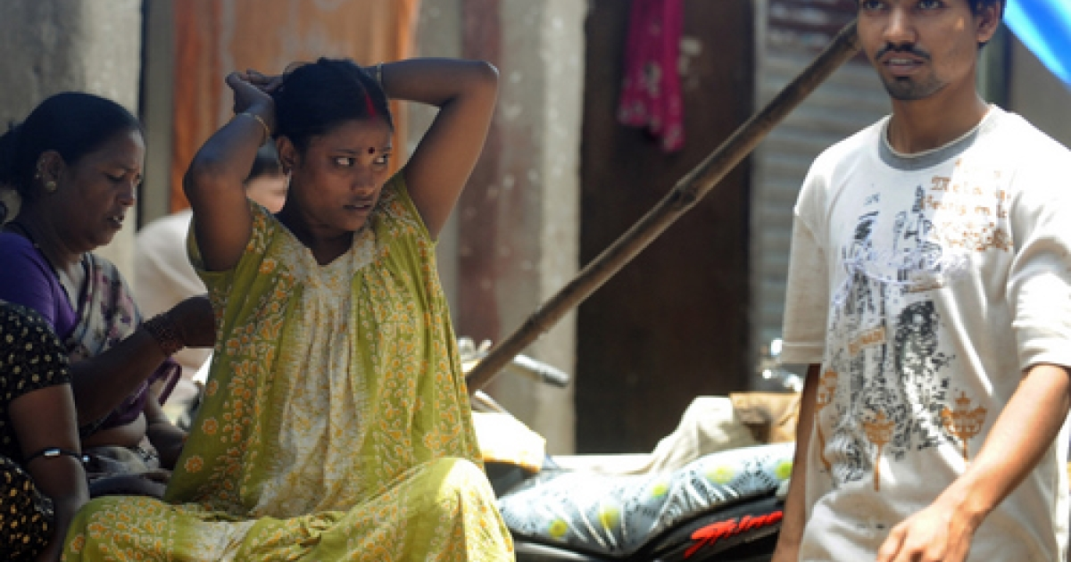 Indian sex workers (L) sit outside their houses in the red light district of Kamathipura in Mumbai on August 23, 2010. Prostitution is illegal in India but police often turn a blind eye to the trade. There are around 1.2 million sex workers in the country, according to the National AIDS Control Organisation.</p>