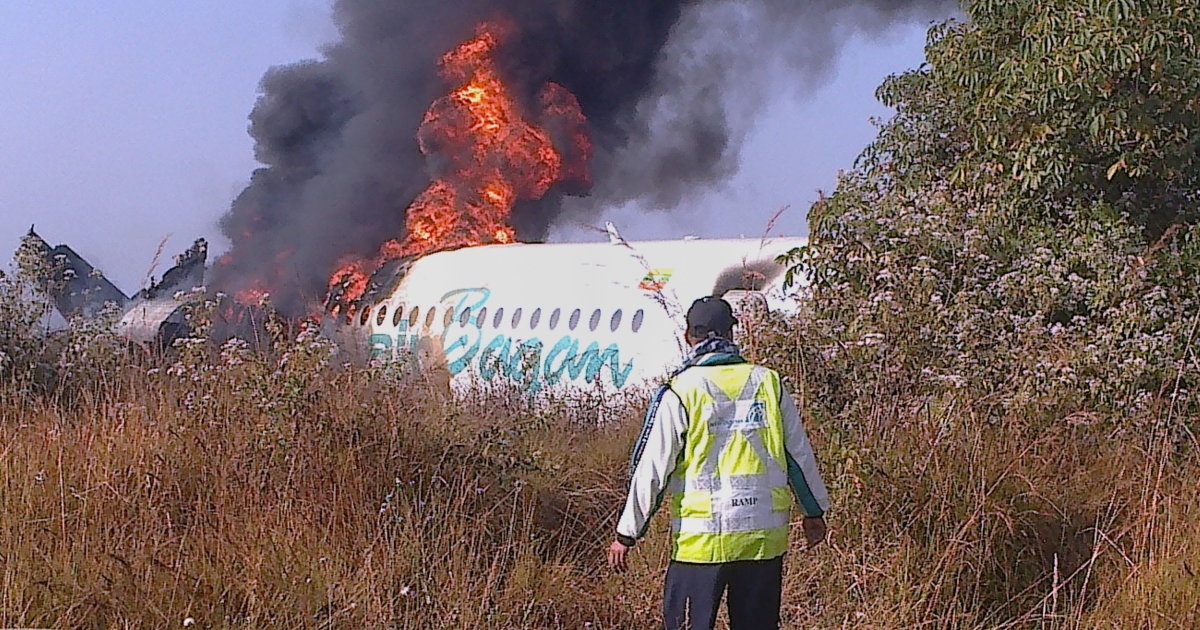 A man walking by a burning Air Bagan passenger plane after it crashed near Heho airport in Myanmar's eastern Shan state. The aged Fokker-100 plane, carrying 65 passengers including foreign tourists, crash-landed. Two are dead and 11 others are injured, the airline and officials said.</p>