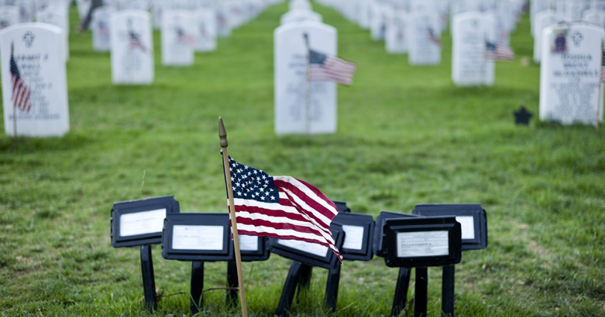 A flag is seen at the temporary marker for a mass grave in Section 60, an area largely used for those who died while serving in the wars in Afghanistan and Iraq, at Arlington National Cemetery May 24, 2012 in Washington, DC, ahead of Memorial Day on May 28, 2012.</p>