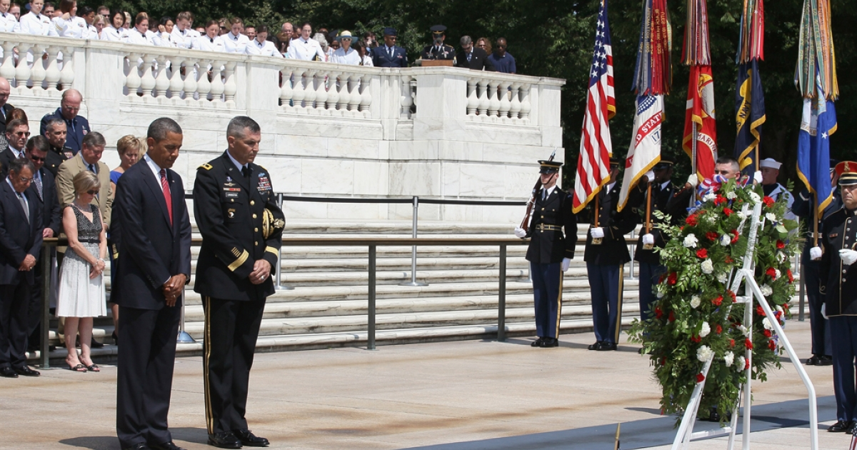 President Barack Obama (L) stands during a moment of silence before placing a commemorative wreath during a ceremony on Memorial Day at the Tomb of the Unknowns at Arlington National Cemetery on May 28, 2012 in Arlington, Virginia. For Memorial Day President Obama is paying tribute to military veterans past and present who have served and sacrificed their lives for their country.</p>
