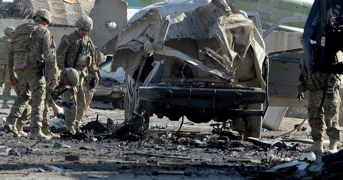 US soldiers inspect the site of a suicide attack near the gate of Kandahar international airport on January 19, 2012.  A suicide bomber killed at least seven people and wounded eight on January 19 in an attack at Kandahar international airport in war-torn southern Afghanistan, officials said.</p>