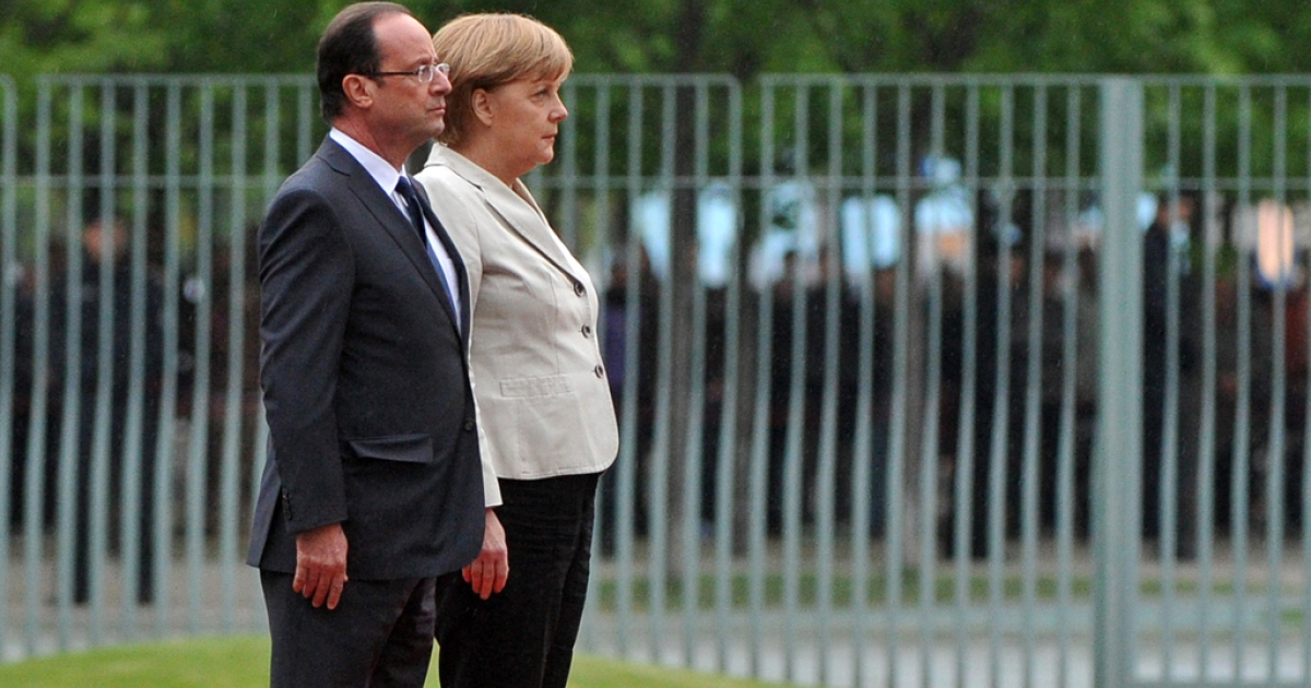 German chancellor Angela Merkel (R) and the new French president Francois Hollande listen to their national anthems at the German Chancellery on May 15, 2012 in Berlin. Francois Hollande meets Angela Merkel for their first talks on the debt crisis as Greece's future in the eurozone appears uncertain before giving a news conference and sharing a working dinner.</p>