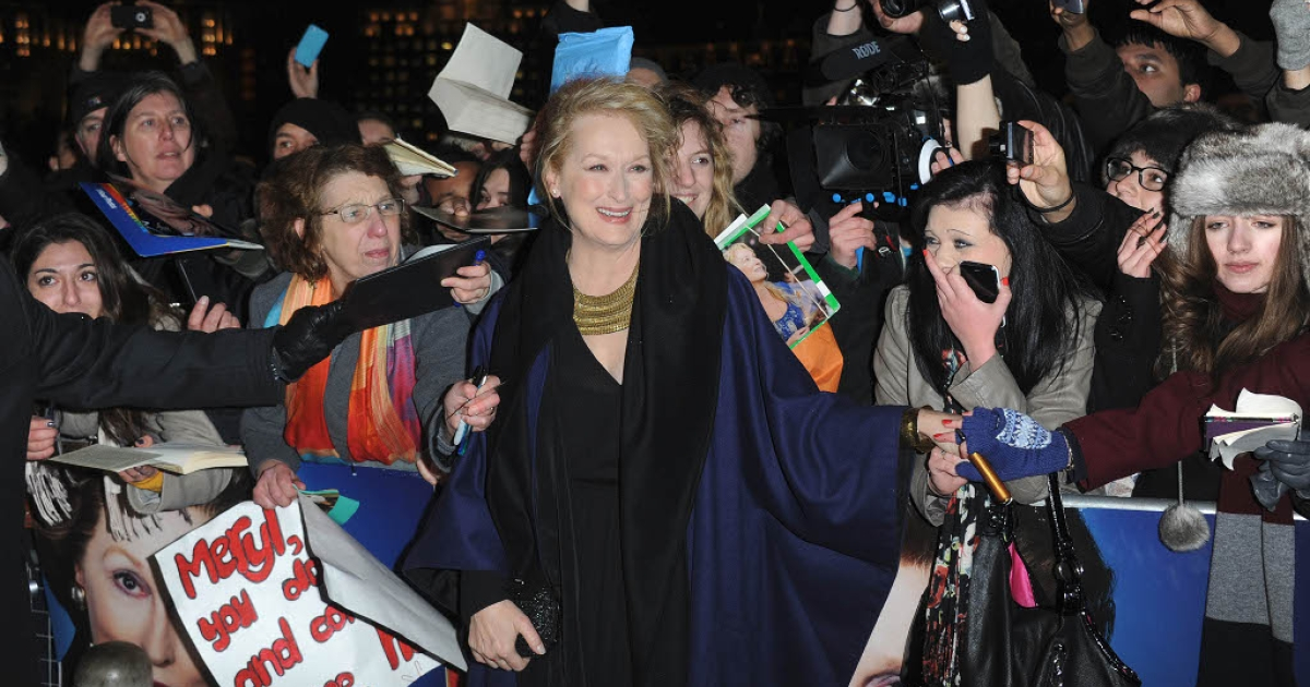 Meryl Streep greets fans who braved gale force winds and rain to watch her walk the red carpet at Wednesday's gala premier of