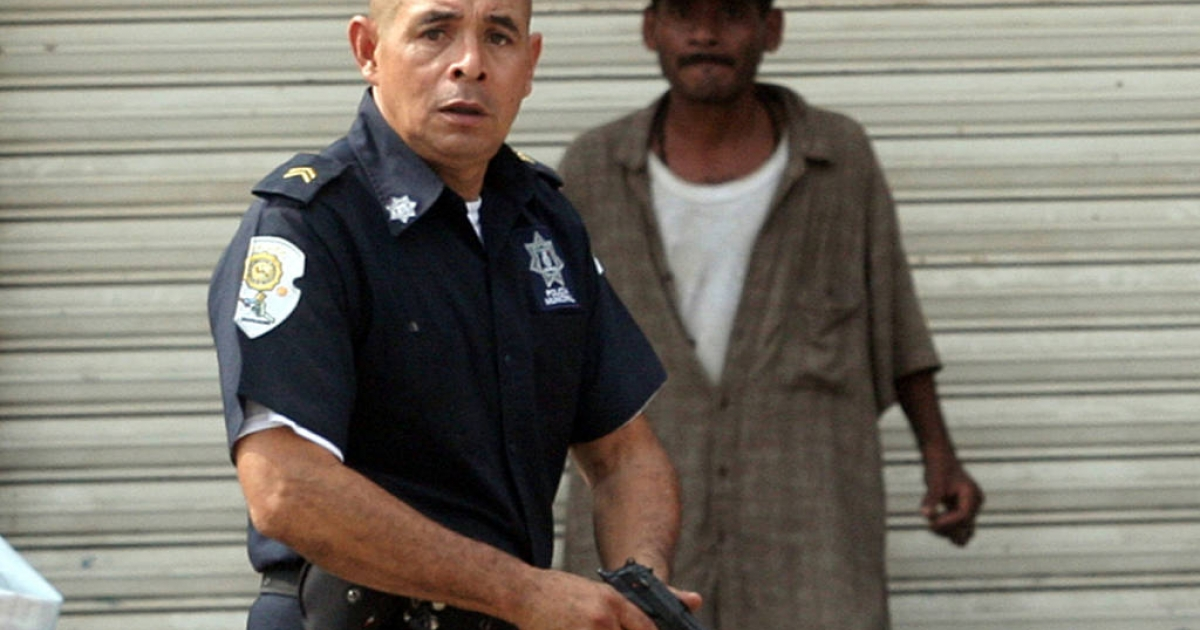 A municipal police officer chased members of a gang in Acapulco, Mexico, on January 8, 2011, after twenty-five bodies were found in the city. Ten more dead were found there on June 9, and over 40,000 people in Mexico have been killed in drug-related violence since December 2006, a surge that many are attributing to lose US gun laws.</p>