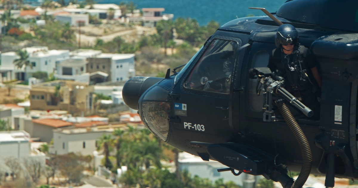 A Mexican Federal Police Officer mans his mini-gun aboard a Mexican Federal Police Black Hawk helicopter on patrol June 15, 2012 over San Jose del Cabo, Mexico.</p>