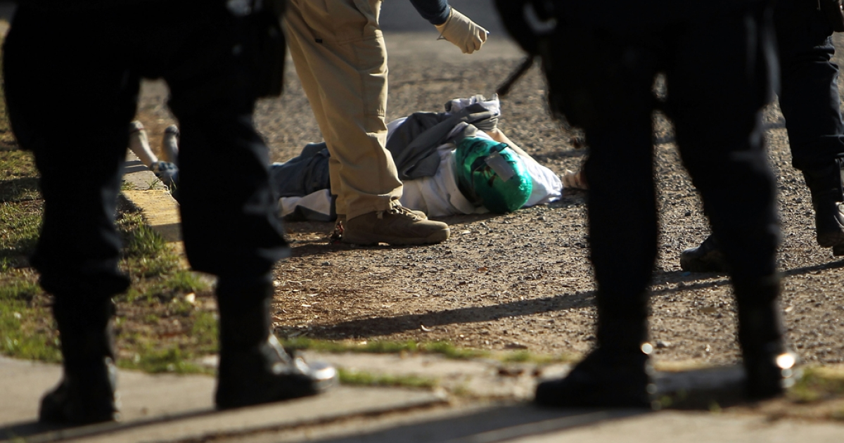 A criminal investigators takes pictures of a body with a mask in the street, one of numerous murders over a 24 hour period, on March 26, 2010 in Juarez, Mexico.</p>