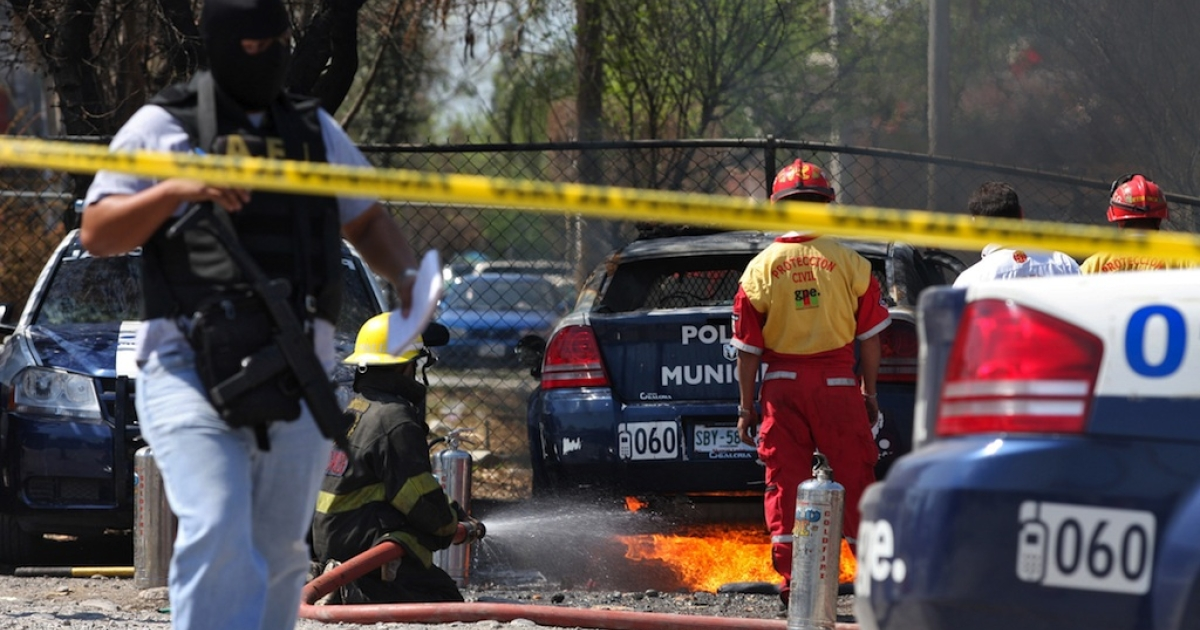 A policeman walks next to firefighters as they extinguish a fire at the Police Station of Guadalupe municipality, Nuevo Leon state, Mexico, after an attack of gunmen, on March 2, 2011.</p>