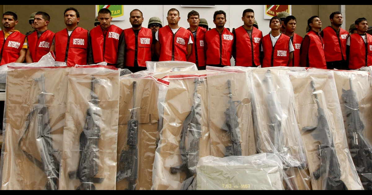 Fourteen alleged members of Los Zetas drug cartel and seized weapons are presented to the press in Monterrey, Mexico on Feb. 15. Many Mexicans wonder why the country cannot return to the peaceful days when governments struck deals with cartels.</p>