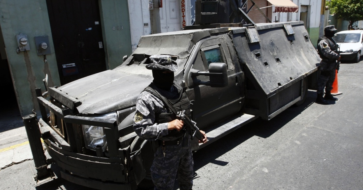 Mexican policemen stand guard next to an armored car belonging to alleged members of the Mexican drug cartel