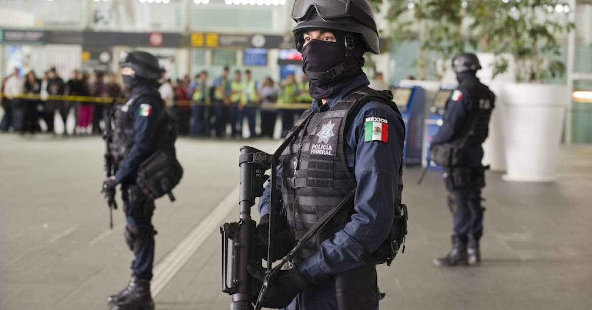 Federal police officers stand guard outside the food court of Mexico City International Airport after the deadly June 25 shootout.</p>