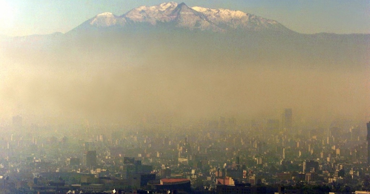 Pollution blankets Mexico City against a backdrop of the Iztaccihuatl volcano.</p>
