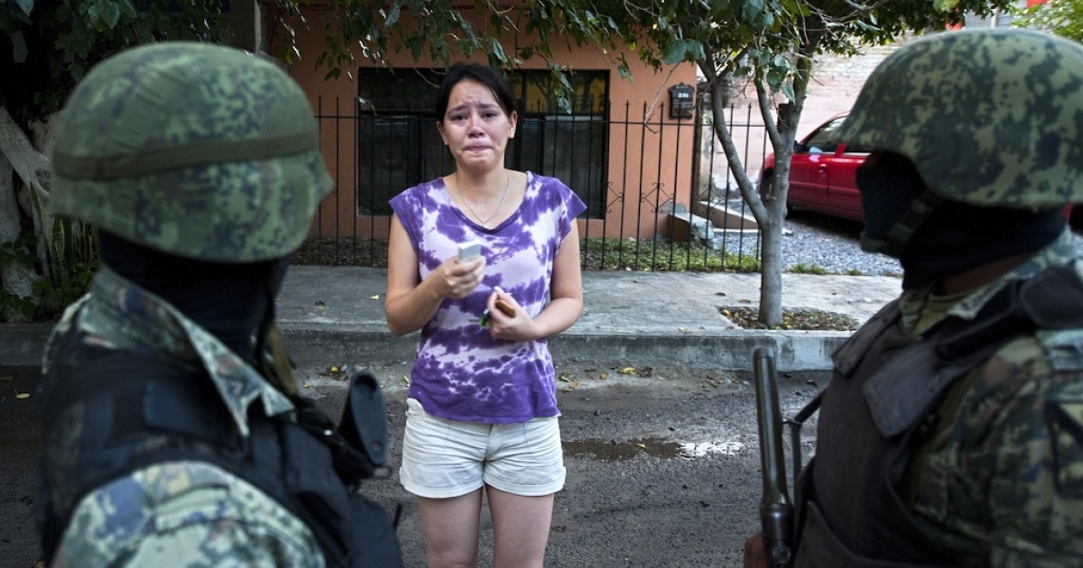 Mexican soldiers listen a distressed woman near Televisa TV network where a car bomb exploded early Friday in the northeastern city Ciudad Victoria, Tamaulipas state on Aug. 27, 2010. The Gulf of Mexico drug cartel was then engaged with the Zetas drug cartel in a bitter turf war for control of Tamaulipas smuggling routes into the United States.</p>