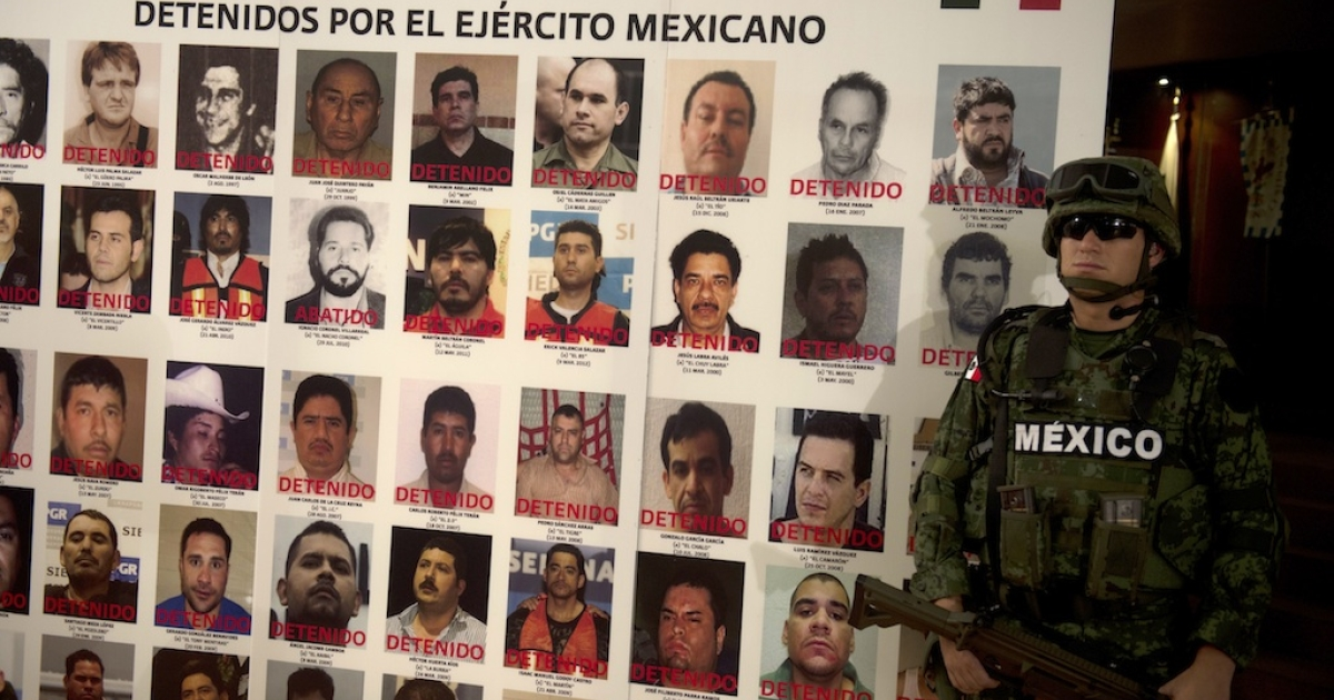 A Mexican soldier stands beside a poster with pictures of alleged drug cartel members arrested during the army-led offensive against the powerful gangs.</p>