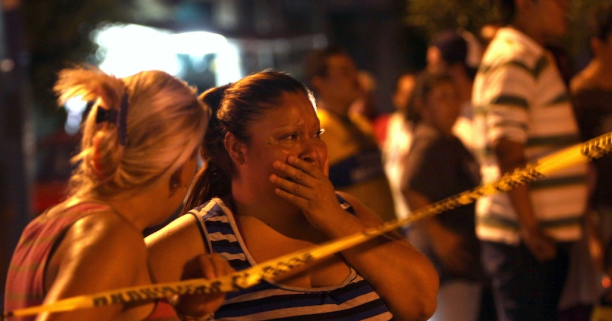 Two women react after seeing the bodies of two of four men killed on a street in Monterrey, Nuevo Leon state, Mexico, on June 18, 2012. More than 50,000 people have been killed since President Felipe Calderon launched a crackdown on the drug cartels in December 2006.</p>