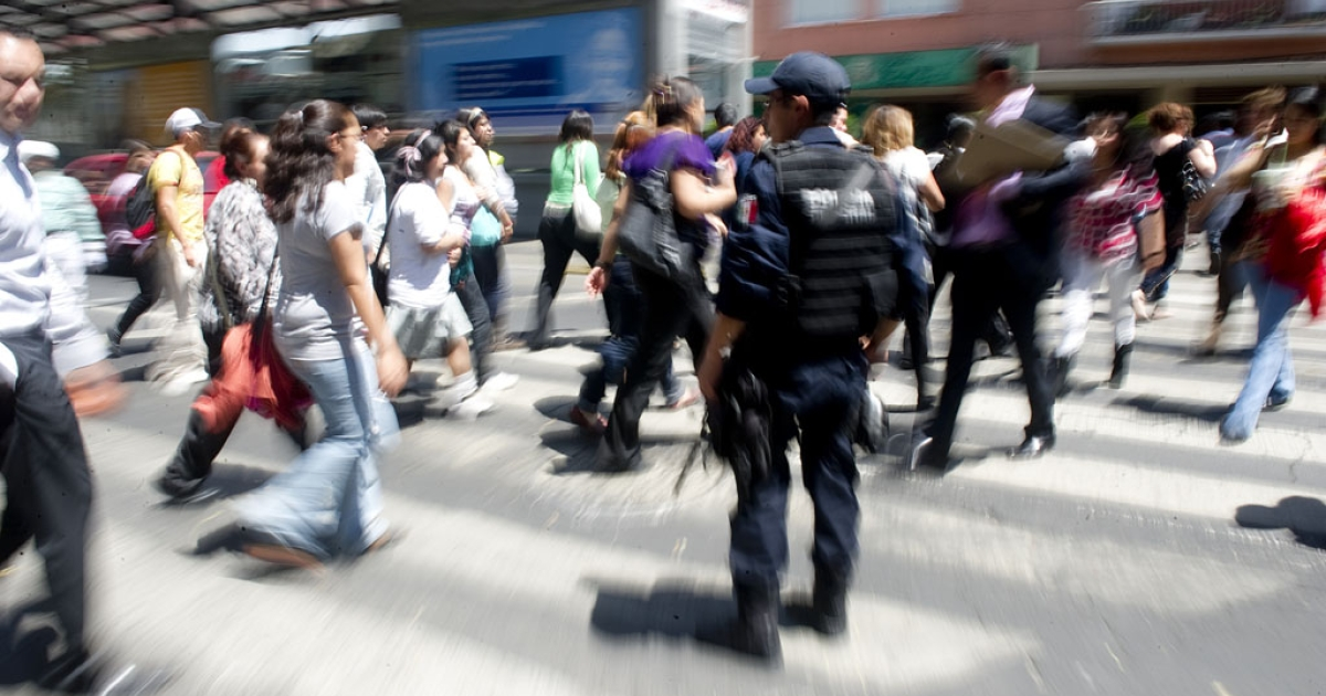 A federal policeman stops the traffic to let people evacuating buildings to cross the street in Mexico City following a strong quake that hit Mexico on March 20, 2012.</p>