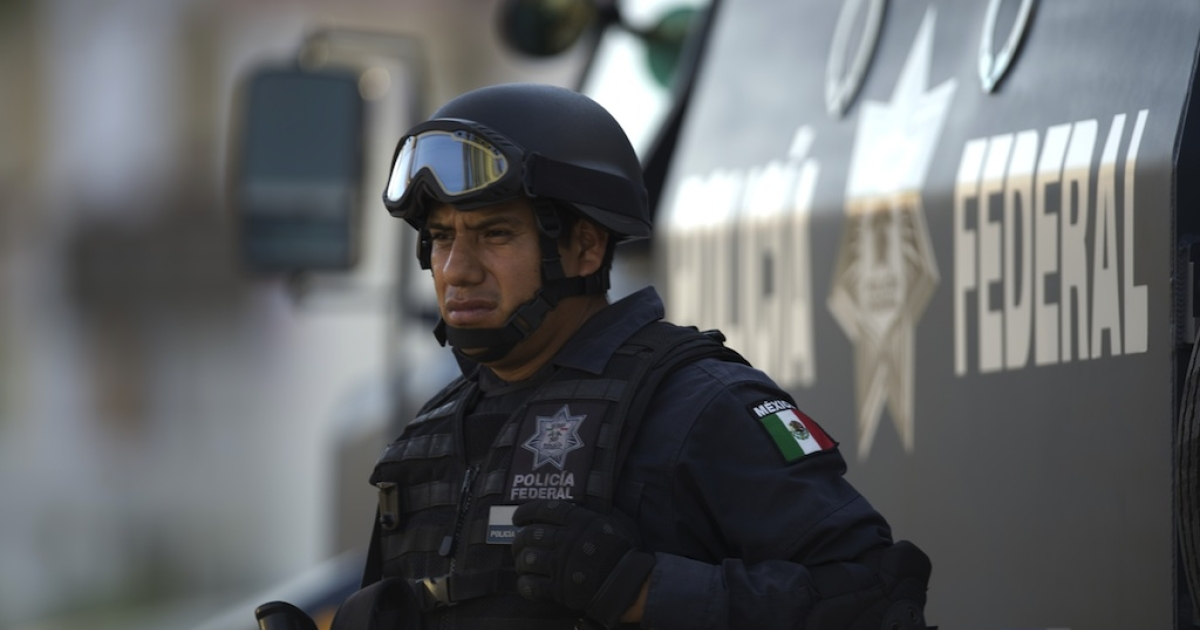 A Mexican federal policeman stands next to an armoured vehicle at a checkpoint in the Mexican resort of San Jose del Cabo on June 16, 2012.</p>