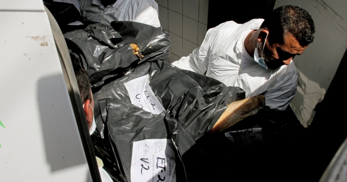 Forensic technicians unload from a van to the morgue, some of the 15 corpses found earlier on May 9 in two abandoned vehicles on the highway to Chapala.</p>