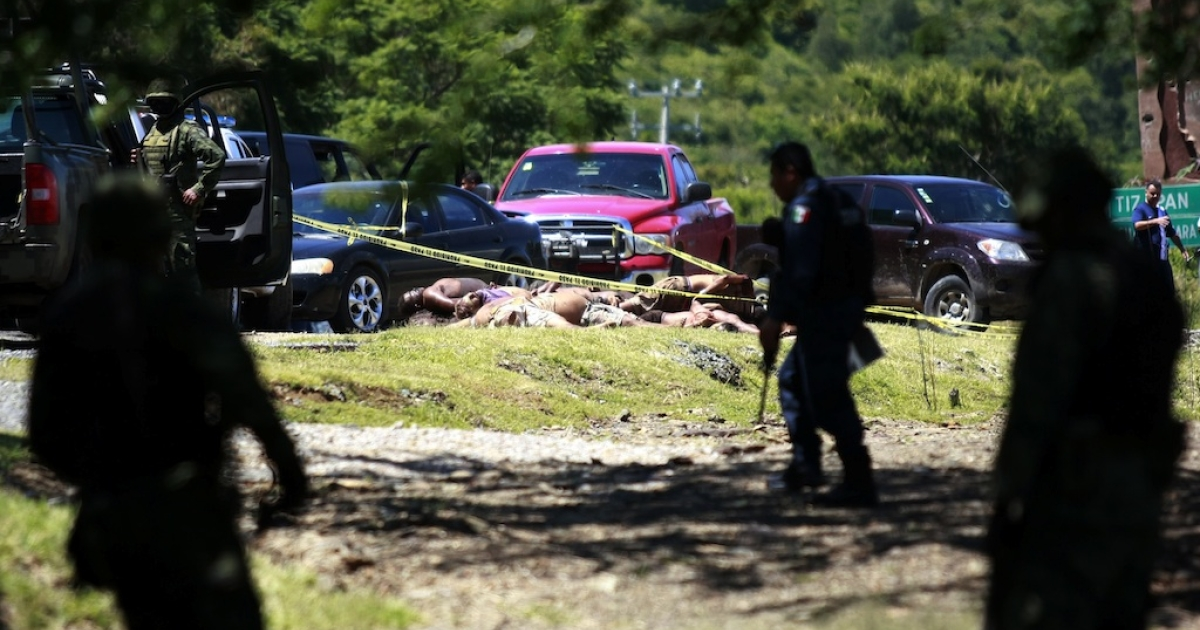 Mexican soldiers and federal police patrol the area where the bodies of 17 men were found next to a road in the central-west state of Jalisco, Mexico, on September 16.</p>