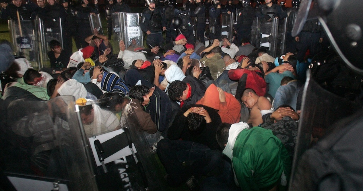 Mexican policemen surround a group of students under arrest after a violent protest in Michoacan State, on October 15, 2012. Protests have taken place all over the country in the shadow of a labor reform bill that will likely be passed in the Senate.</p>