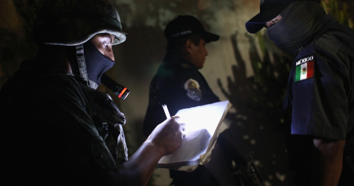 A Mexican soldier takes notes at a suspected drug-related murder site on March 3, 2012 in Acapulco.</p>