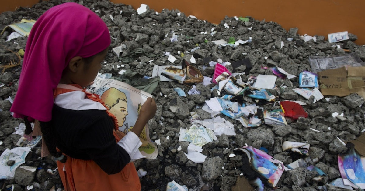 A girl wearing the style of clothes required by the Virgin of the Rosary sect in the Mexican state of Michoacan walks through the rubble of a primary school on July 18, 2012. The building was destroyed by conservative followers of the group, who claimed mainstream schools were introducing vice into their community.</p>
