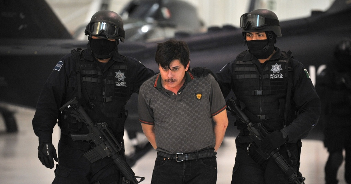 Mexican police escort Jaime Herrera Herrera, 'El Viejito', an alleged member of the Joaquin 'El Chapo' Guzman's drug smuggling cartel, to be photographed by the media in Mexico City on Feb. 14.</p>