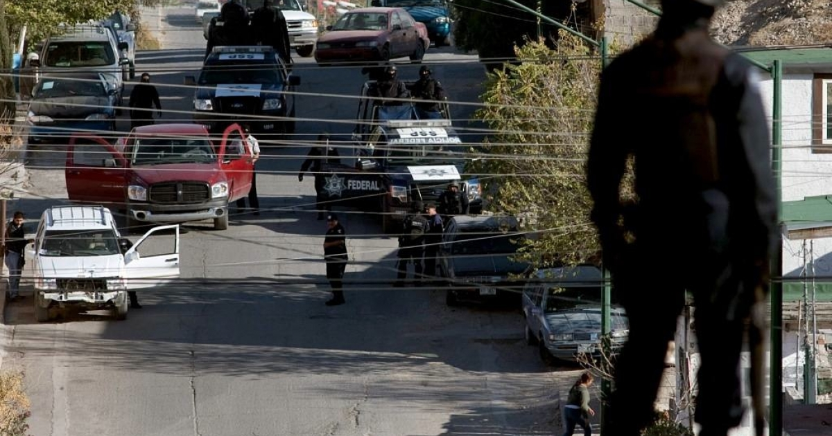 A member of the Federal Police looked on at a crime scene in Ciudad Juarez, Mexico, in Dec. 2010 after three police officers were killed.</p>