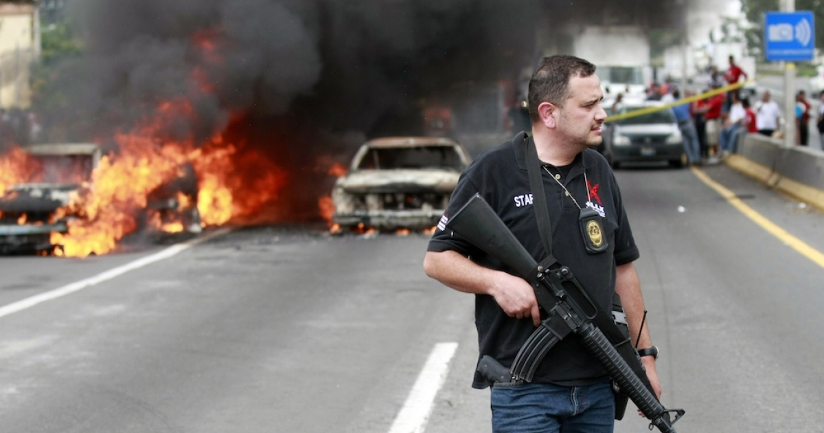 A policeman stands guard near burning cars on a highway in Guadalajara, the capital of Jalisco state, Mexico, on August 25, 2012.</p>