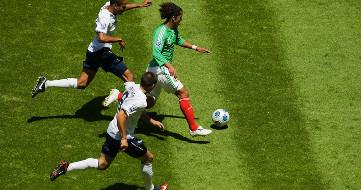 Mexico's Francisco Fonseca dribbles between Carlos Bocanegra and Oguchi Onyewu during the 2006 FIFA World Cup qualifying match on March 27, 2005 at Estadio Azteca in Mexico City, Mexico. Mexico won 2-1.</p>