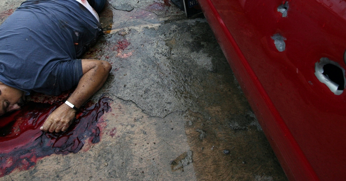 A corpse lies on the floor next to a car outside a house in Acapulco, Guerrero state, Mexico on September 2010. Seven people were killed with AK-47 assault rifles during a suspected clash between drug dealers.</p>