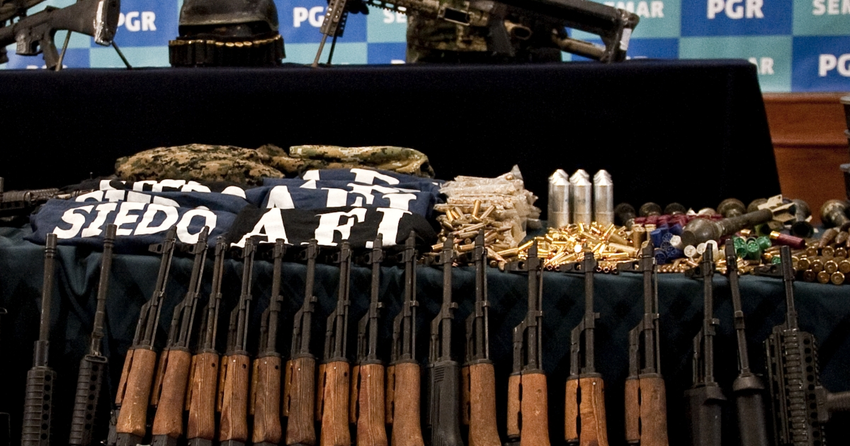 A member of the Mexican Navy stands next to guns seized in the arrest of Raul Hernandez Lechuga (not in frame) -- an alleged member of the drugs cartel 'Los Zetas' -- displayed during a presentation to the news media in Mexico City on Dec 13.</p>