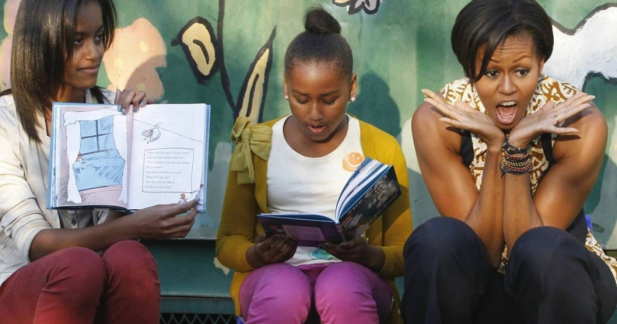 Michelle Obama entertains children while she takes turns with daughters Sasha, left, and Malia by reading