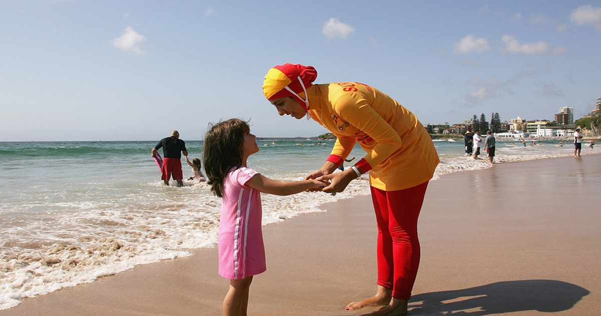Mecca Laa Laa talks to a young girl whilst wearing a 'Burqini' on her first surf lifesaving patrol at North Cronulla Beach February 4, 2007 in Sydney, Australia. The red and yellow 'Burqini' was specially designed for Muslim lifesavers to allow females to fulfil both their patrolling and religious obligations.</p>